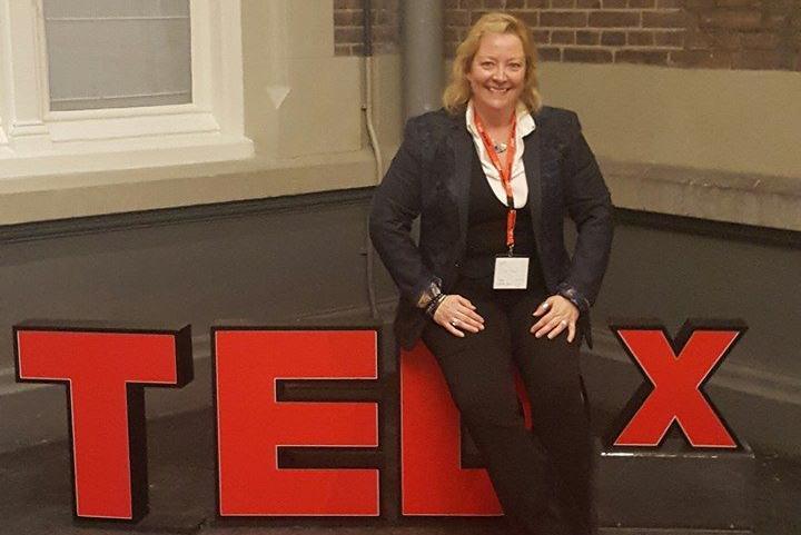 Barbara Rogoski Sitting on the TEDx Sign